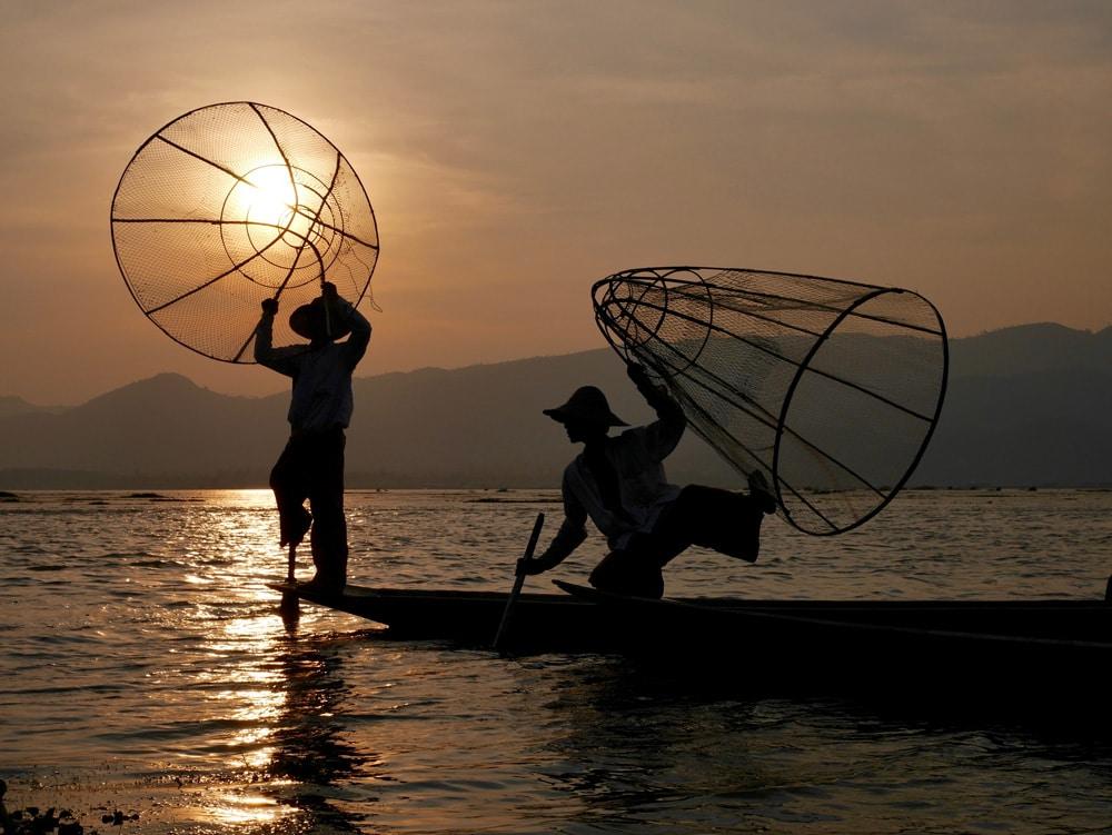Des pêcheurs prennent la pose au coucher du soleil sur le lac Inle au Myanmar